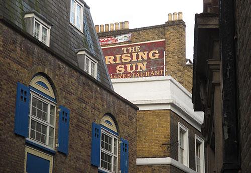 Hausfassade mit Werbung für The Rising Sun