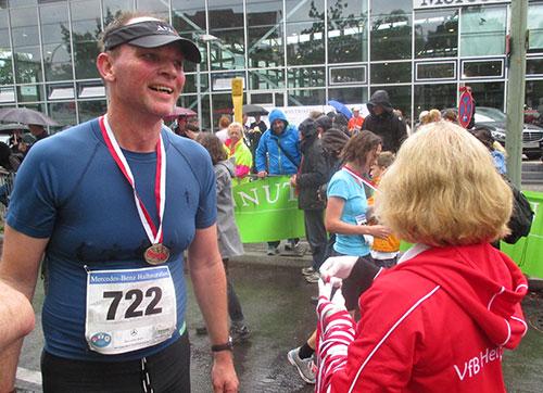 Läufer bekommt Medaille im Ziel des Tegel-Halbmarathon