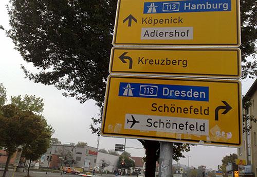 Gelbes Schild mit blauen Autobahnhinweisen