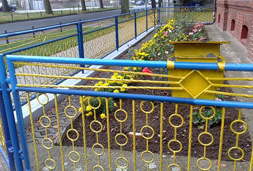 blau-gelber Metallzaun mit gelbem Briefkasten