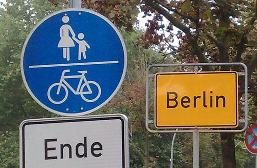 Gelbes Ortsschild Berlin und blaues Schild Fußweg