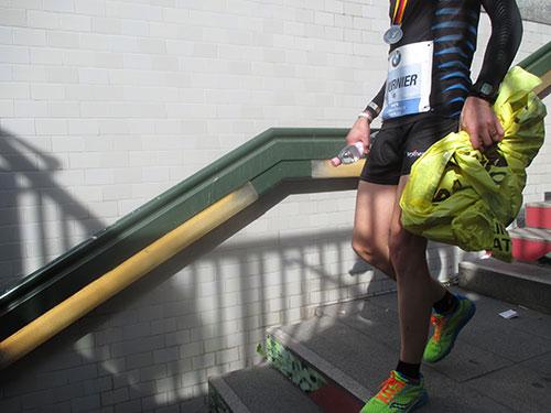 Marathon-Läufer nach dem Rennen auf U-Bahn-Treppe