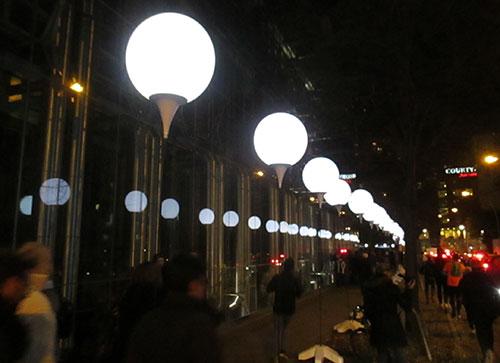 Leuchtende Ballons der Lichtgrenze spiegeln sich im bürogebäude an der Axel-Springer-Straße