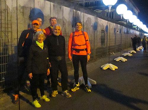 Läufergruppe vor Resten der Berliner Mauer an der Niederkirchnerstraße