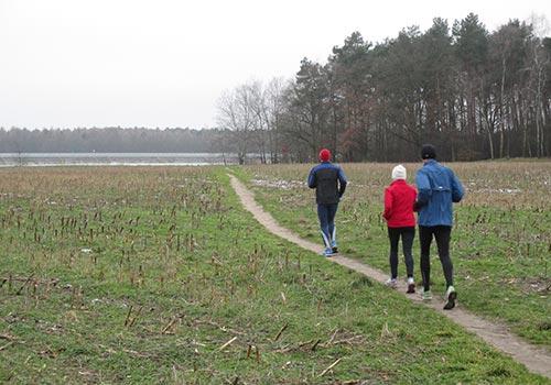 Läufer auf schmalem Pfad über ein Feld