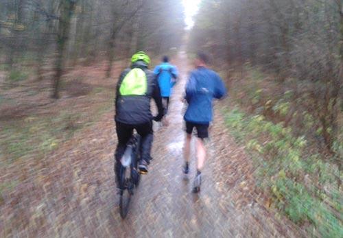 Läufer mit Fahrradbegleitung im Regen