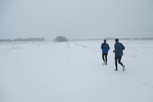 Läufer in einer weiten Schneelandschaft