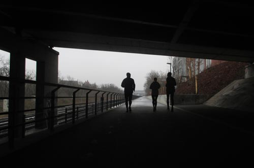 Läufer-Umrisse unter Brücke