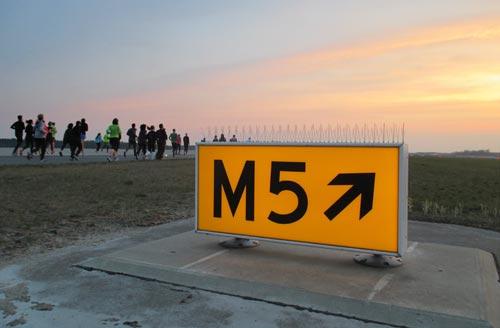 Schild auf Startbahn des BER Berlin-Brandenburg mit Läufern im Hintergrund
