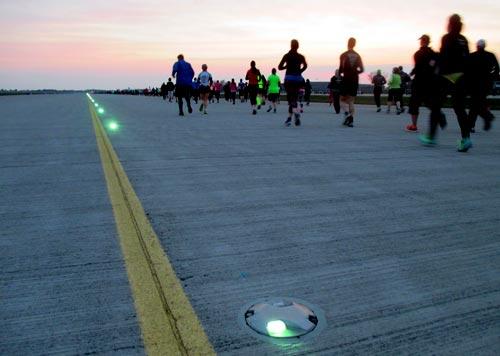 Läufer neben Startbahnbeleuchtung