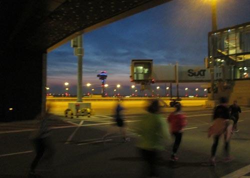 Läufer auf dem neuen Flughafen BER bei Abendbeleuchtung