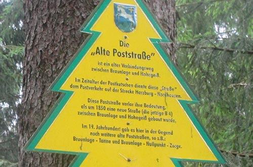 Ein Schild in Form eines Tannenbaums erzählt die Geschichte der Alten Poststraße