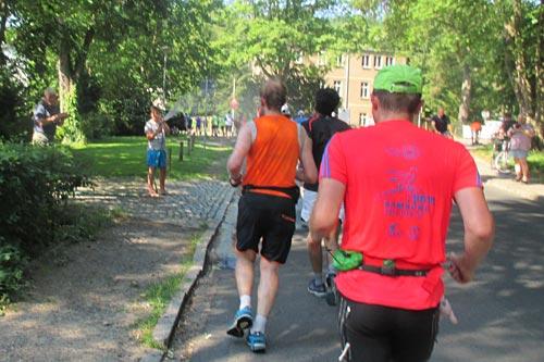 Anwohner mit Gartenschlauch erfrischt die Halbmarathon-Läufer in der Hitze