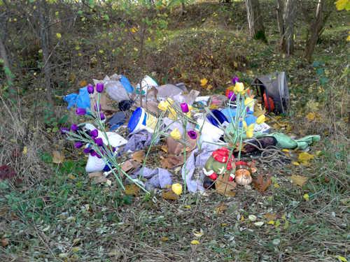 Illegaler Müll, mit Blumen dekoriert