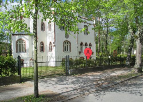 Haus mit großem roten Google-Pin im Vorgarten