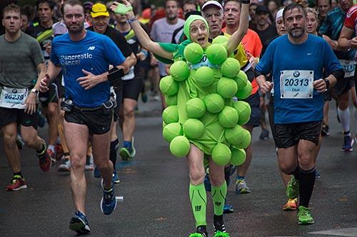 Marathon-Läuferin als Weintraube mit grünen Bällen