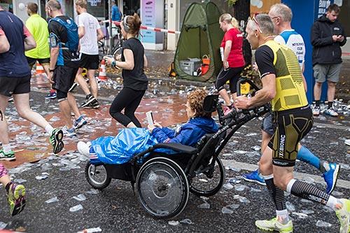 Läufer schiebt lesende Frau im Rollstuhl