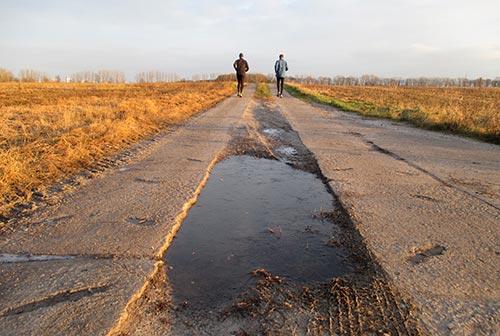 Läufer auf Plattenweg zwischen den Feldern