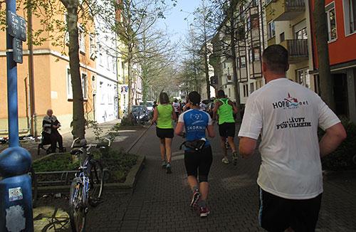 Halbmarathon-Läufer in schattiger Straße