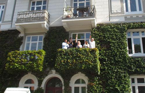 Zuschauer auf efeubewachsenem Balkon