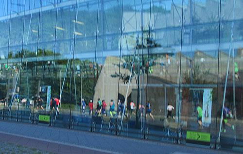 Läufer spiegeln sich in einer Glasfassade