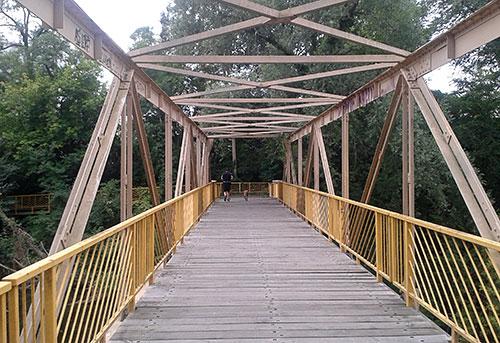 Läufer auf Brücke mit gelbem Geländer