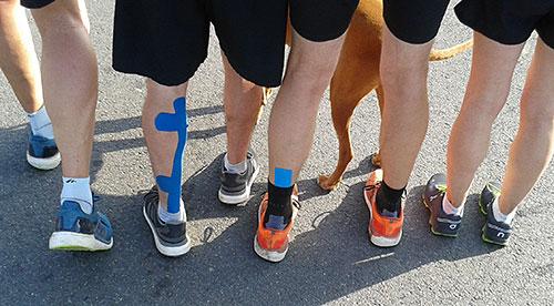 Läuferbeine mit blauen Kinesio-Tapes