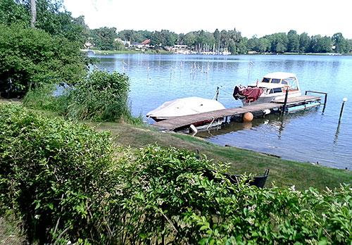 Blick auf den See mit Steg und Booten