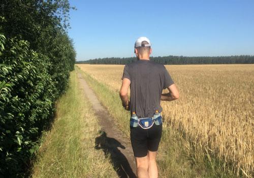 Läufer an einem Feldrand in der Morgensonne