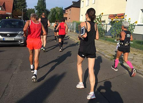 Läuferinnen und Läufer in den kleinen Straßen