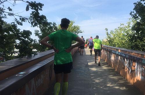 Oben auf der Fußgängerbrücke gehen viele Läufer
