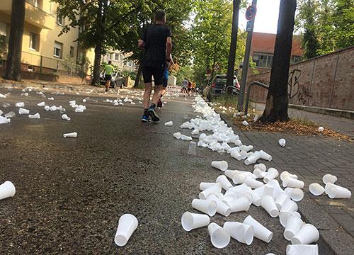 Becher auf der Straße nach dem letzten Getränkestand vor dem Ziel