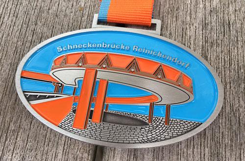 Medaille des Tegel-Halbmarathon 2019 mit Motiv Schneckenbrücke