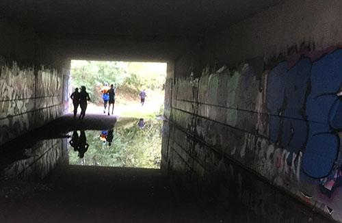 Läufer im Tunnel spiegeln sich in einer großen Pfütze