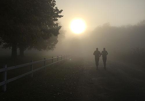Läufer im Gegenlicht der aufgehenden Sonne