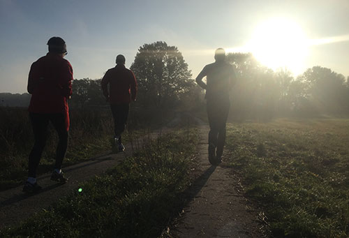 Läufergruppe vor aufgehender Sonne