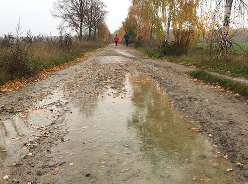 Pfütze im Nieselregen, im Hintergrund Läufer