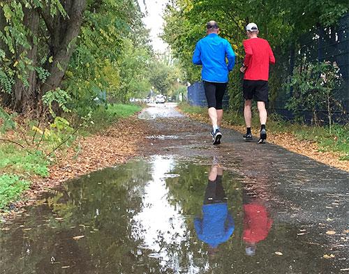 Läufer spiegeln sich in großer Regenpfütze