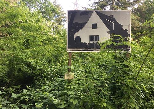 Schild mit Foto eines Hauses von 1938 im Gebüsch