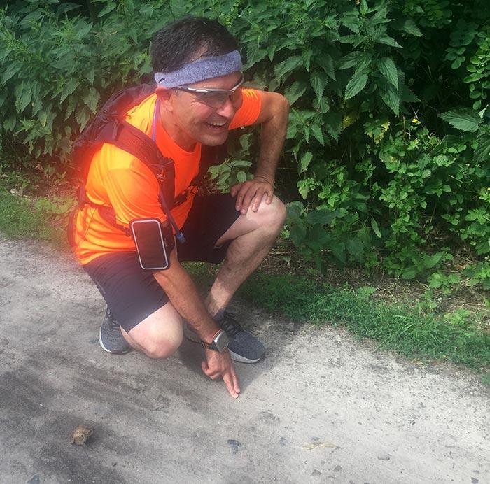 Läufer in Startposition neben Frosch