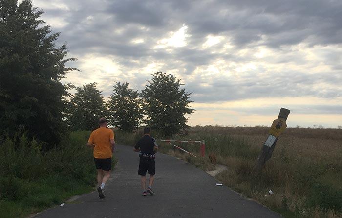 Läufer vor dunklem Himmel