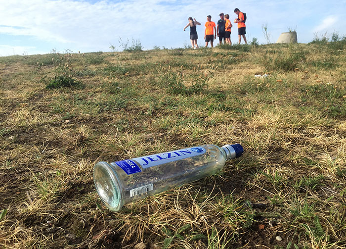 Leere Flasche Wodka, im Hintergrund Läufer-Gruppe