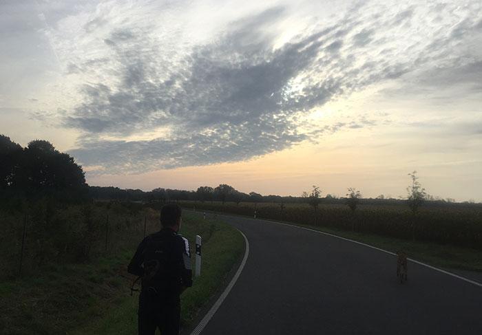 Läufer vor einem bizarren Wolkenhimmel