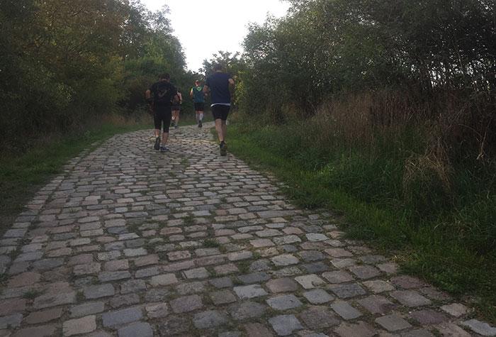 Läufer laufen Steigung mit Kopfsteinpflaster im Park hinauf