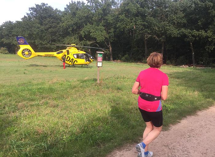Läuferin läuft an einem auf einer Wiese gelandeten ADAC-Hubschrauber vorbei