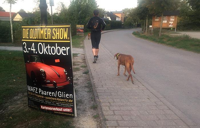 """Läufer mit Hunden, im Vordergrund ein Plakat """"Die Oldtimer Show"""""""