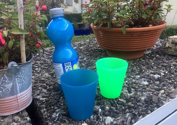 Blaue Flasche mit Iso-Getränk, davor zwei Plastikbecher