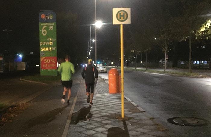 Läufer im Morgendunkel an einer Straße