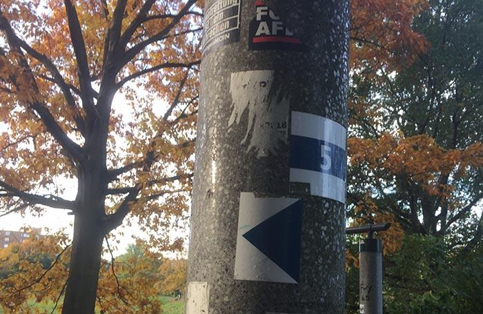 Aufkleber an einem Mast: Weiße 5 auf blauem Grund