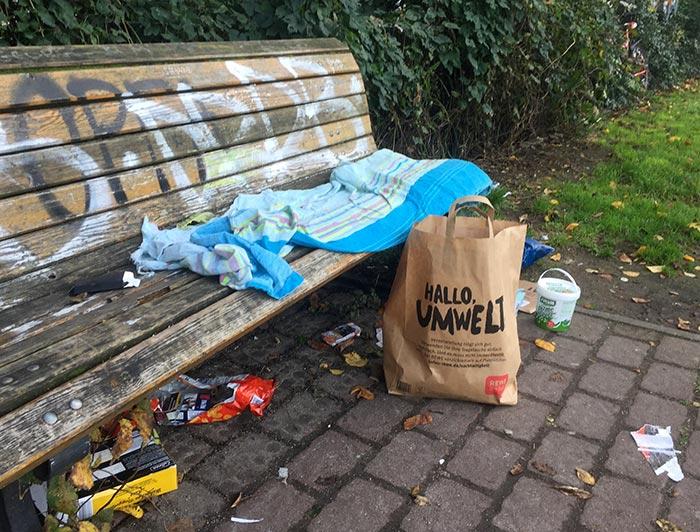 """Parkbank mit alter Decke und Müll, davor Papiertüte mit Aufdruck """"Hallo, Umwelt"""""""